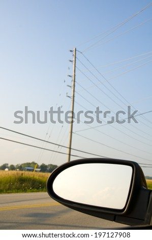 A side mirror of a car driving past some power lines. - stock photo