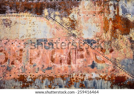 A side panel of an old railroad car is covered with rust, peeling paint, and old rivets in a post-industrial abstract background. - stock photo
