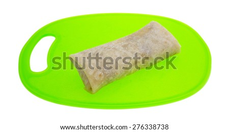 A side view of a chimichanga chicken and cheese burrito on a green cutting board. - stock photo
