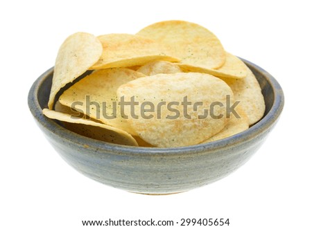 A side view of a gray ceramic bowl filled with generic sour cream and onion potato chips. - stock photo