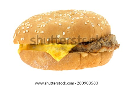 A side view of a prepared frozen cheeseburger in a sesame seed bun. - stock photo