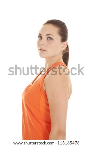 A side view of a woman in her orange workout top looking at camera
