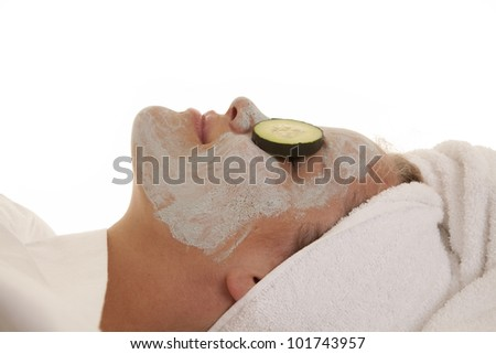 A side view of a woman with a face mask and cucumbers on her eyes.