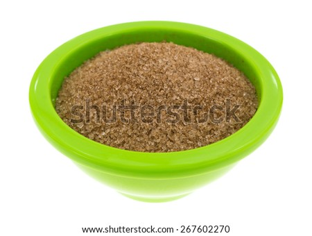 A side view of cinnamon sugar granules in a bright green bowl. - stock photo