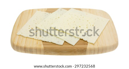 A side view of three slices of Havarti cheese on a wooden cutting board. - stock photo