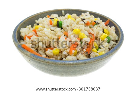 A side view of wild rice and mixed vegetables in a gray bowl.