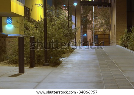 A sidewalk between buildings well lit up at night time. - stock photo