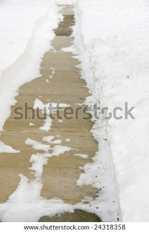 A sidewalk that had been recently shoveled to remove snow - stock photo