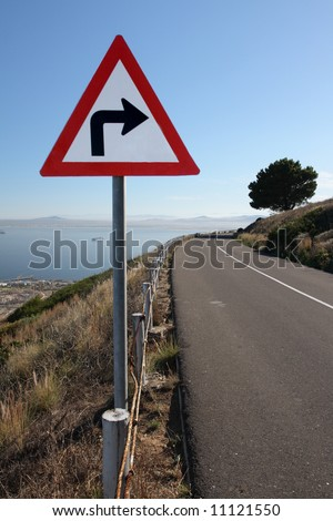 A sighn indicating a right turn of a road on a hill. - stock photo