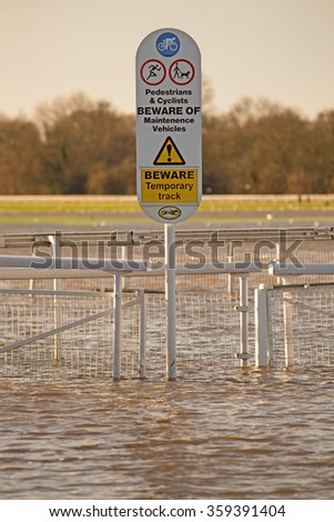 A sign at a racecourse standing in floodwater suggesting this is a 'temporary surface' - stock photo