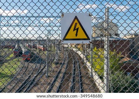 "A sign ""Caution, high energy"" on the background of railroad rails"