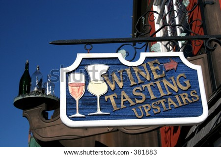 A sign directs customers upstairs for wine tasting.