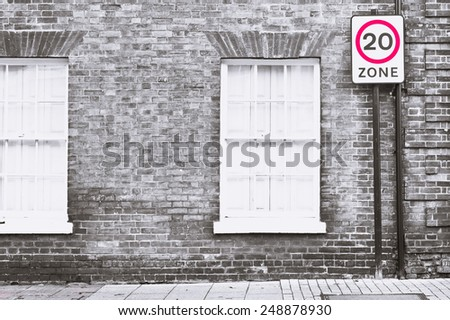 A sign for a 20 mile per hour speed limit zone - stock photo