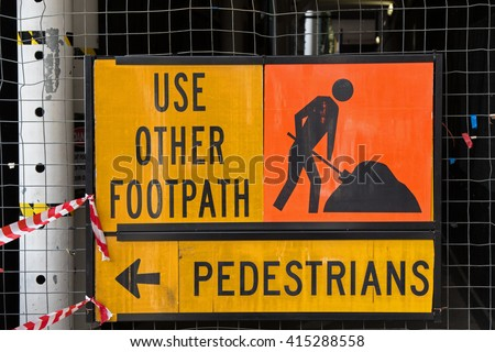A sign for pedestrians to Use Other Footpath in yellow and orange color attached to metal net fence.  - stock photo