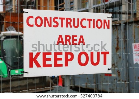 A sign in bold red English is posted outside a construction site warning people too keep out/Keep Out Construction Sign/A sign in English is posted on a construction site warning people too keep out.
