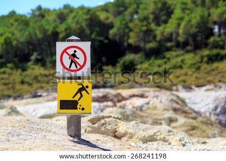 A sign indicating not to trespass and danger of falling - stock photo