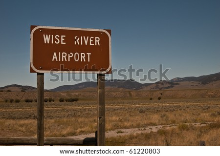 a sign indicating the location of the Wise River Airport, showing the mountains of Montana in the background