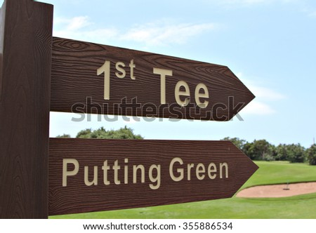A sign on a golf course indicates the direction to the first tee and the putting green at a country club. - stock photo