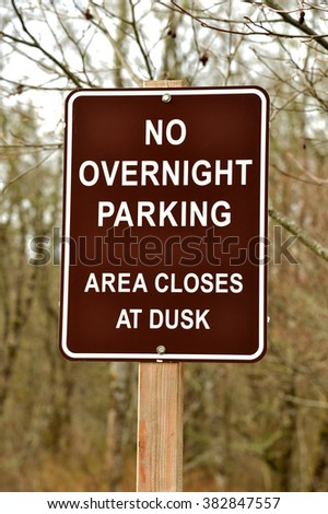 a sign on a wooden post stating that no overnight parking is permitted in the area