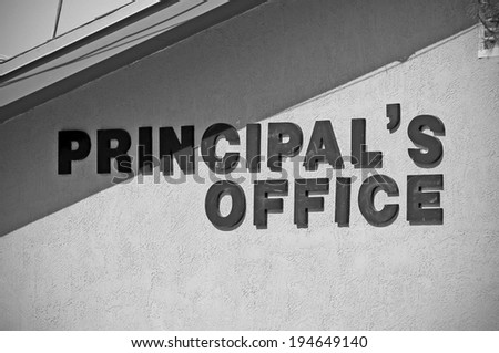 A sign on the side of a school building shows where the principal's office is located. - stock photo
