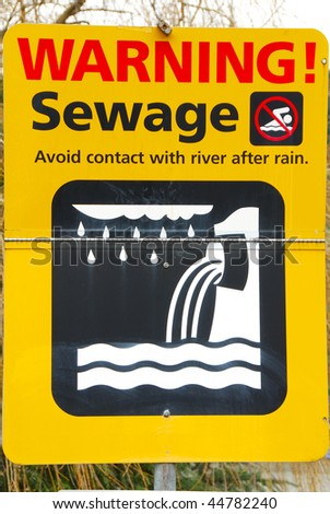 A sign on the Willamette River dock warning of sewage after a storm in Portland Oregon - stock photo