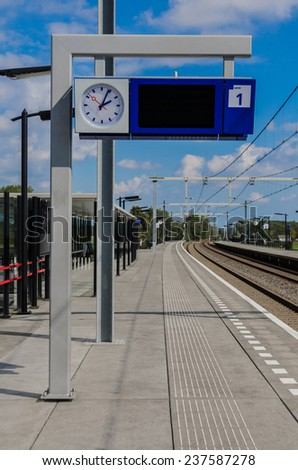 A sign posts information about departing trains at a train station in the Netherlands - stock photo
