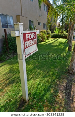 """A sign proclaiming """"FOR RENT"""" stands in front of an apartment building. - stock photo"""