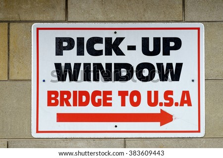 A sign reading 'Pick up Window Bridge to U.S.A.' with an arrow pointing the direction outside a building in Niagara Falls Ontario Canada.
