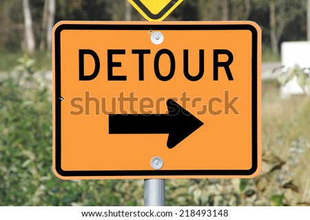 A sign used to inform motorists that they'll have to use an alternate route/Detour Sign/A sign used to inform motorists that they'll have to use an alternate route - stock photo