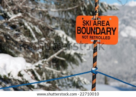 A sign warns skiers and snowboarders that the are they are about to enter is out of bounds and not patrolled. - stock photo