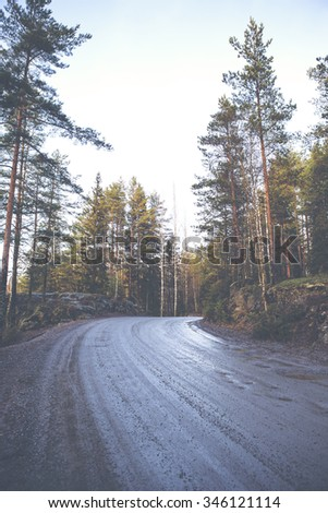 A silent and wet road in Finland. The road is in an awful condition. The road is filled with holes and water. Curve is turning to right. Image has a vintage effect applied.