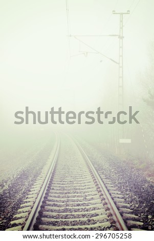 A silent railroad on a foggy morning. Image has a vintage effect applied.