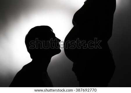A silhouette couple in expectations kissing on belly - stock photo