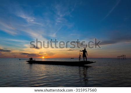 A Silhouette Fisherman Catching Fish from square dip net at Pak Pra Canal in early morning during golden sunrise moment - stock photo