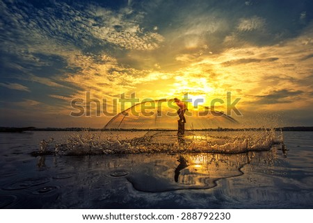 A silhouette fisherman throw a net during sunrise, Thailand - stock photo