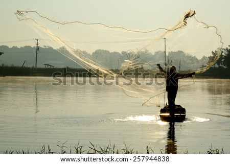 A silhouette fisherman throw a net to catch a fish in a river - stock photo