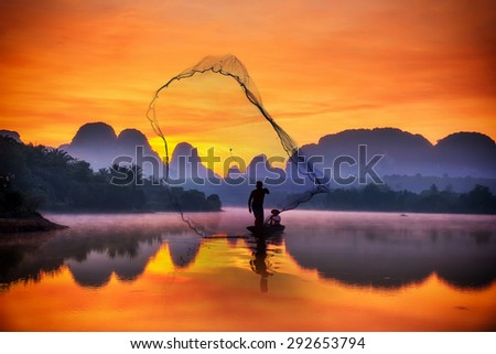 A silhouette fisherman throw a net to catch a fish in a river with morning - stock photo