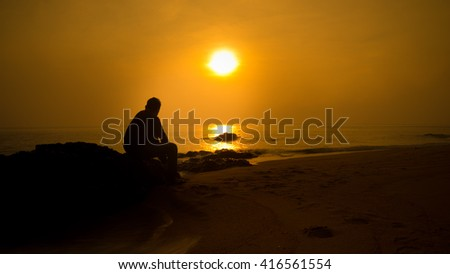A silhouette man on the beach and sunrise moment at background with yellow gel filter view.