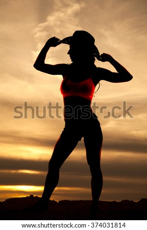 A silhouette of a beautiful cowgirl in the sunset. - stock photo
