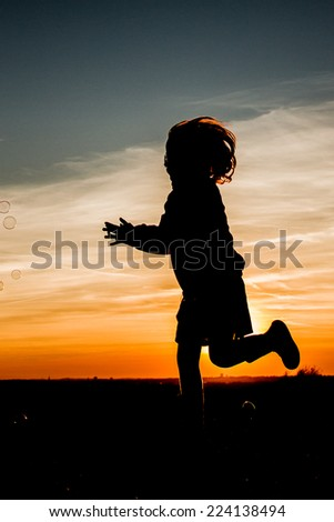 A silhouette of a child having fun with soap bubbles in the sunset