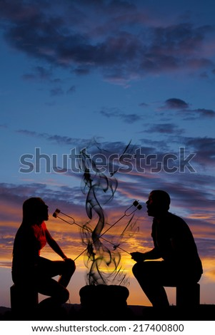 A silhouette of a couple eating and roasting marshmallows over a camp fire. - stock photo