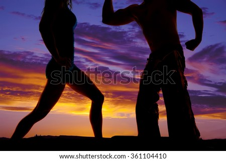 A silhouette of a couple with their bodies up close the cowboy with his chaps. - stock photo