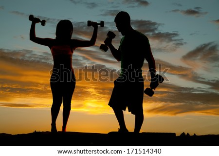 a silhouette of a couple working out with weights. - stock photo