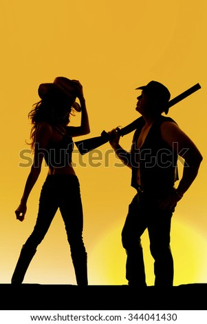 A silhouette of a cowboy and cowgirl together, he is holding on to his rifle. - stock photo