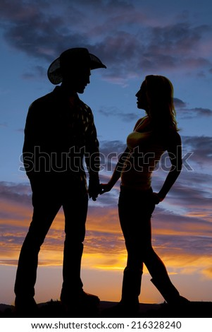 A silhouette of a cowboy and his woman holding hands in the outdoors. - stock photo