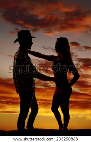 A silhouette of a cowboy and his woman touching in the outdoors. - stock photo