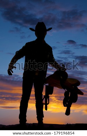 A silhouette of a cowboy holding a saddle in the sunset. - stock photo