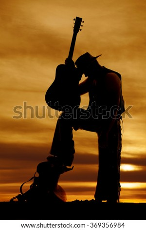 A silhouette of a cowboy holding on his guitar with is head on it. - stock photo