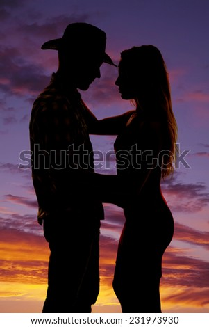 a silhouette of a cowboy holding on to his lady. - stock photo