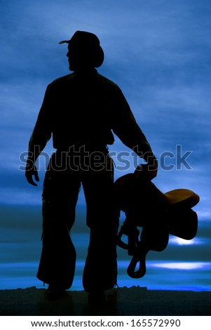a silhouette of a cowboy holding on to his saddle. - stock photo